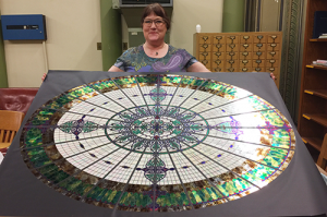 Jane Bergman displays her replica of the glass dome that once overlooked the library in Altgeld Hall.